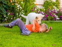 Chiot blanc et enfant suisses du ` s de berger jouant ensemble sur g vert Image libre de droits