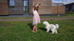 Chiot blond de chien d'alimentation de petite fille dans la cour de maison Tir de mouvement de cardan banque de vidéos