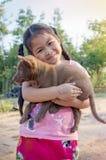 Chiot dans une étreinte d'amour de fille de sourire de l'Asie Photographie stock libre de droits