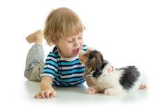 Chiot de baiser drôle de petit garçon d'enfant D'isolement sur le fond blanc Images stock