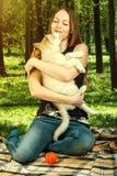 Chiot de chien jouant avec la jeune femme heureuse Photos stock