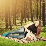 Chiot de chien jouant avec la jeune femme heureuse Photos libres de droits