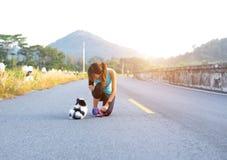 Chiot et jeunes femmes courant l'exercice sur le parc de rue pendant le matin Jeune femme enseignant son gesturi d'obéissance de  photos stock