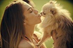 Chiot mignon de spitz de baiser sensuel de femme, animal familier Photo stock