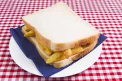 Chip butty. A traditional British chip sandwich (butty) made on white sliced bread served on a white plate with serviette with a checked table cloth background Stock Photos