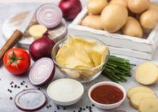 Chip casalinghi organici freschi delle patatine fritte in ciotola di vetro con panna acida e le cipolle rosse sul fondo leggero d immagine stock