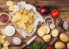 Chip casalinghi organici freschi delle patatine fritte con panna acida e cipolle rosse e spezie su fondo di legno Con giallo fres fotografie stock