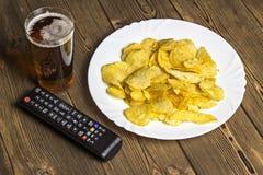 Chip con birra ed il telecomando della TV su una ripresa esterna di legno del fondo fotografia stock libera da diritti