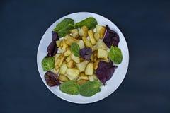 Chip con le varie foglie della lattuga su un fondo di legno scuro Vista da sopra fotografia stock libera da diritti