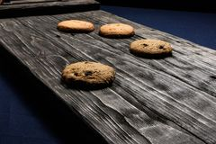 Chip-cookies on a dark old wooden trayon a blue background. stock photos