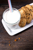 Chip cookies and glass of milk with drinking straws on old woode Stock Photo