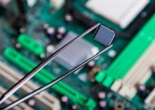 Chip de ordenador con las pinzas, electrónicas imagenes de archivo
