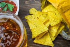 Chip di cereale dei nacho con la salsa classica del pomodoro La birra fredda fresca è perfetta con gli spuntini saporiti Immagine Stock