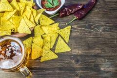 Chip di cereale dei nacho con la salsa classica del pomodoro La birra fredda fresca è perfetta con gli spuntini saporiti Immagini Stock