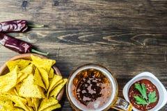 Chip di cereale dei nacho con la salsa classica del pomodoro La birra fredda fresca è perfetta con gli spuntini saporiti Fotografie Stock