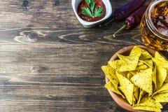 Chip di cereale dei nacho con la salsa classica del pomodoro La birra fredda fresca è perfetta con gli spuntini saporiti Fotografie Stock Libere da Diritti