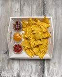 Chip di tortiglia con le immersioni del formaggio, del pomodoro e del barbecue su fondo di legno bianco Spuntino fotografia stock