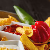 Chip di tortiglia su un piatto blu con la salsa piccante del pomodoro messicano Immagine Stock