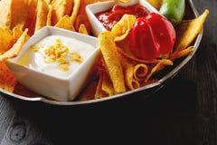 Chip di tortiglia su un piatto blu con la salsa piccante del pomodoro messicano Fotografia Stock