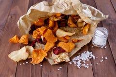 Chip di verdure sani su carta con sale marino Immagine Stock