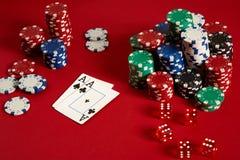 Chip ed assi di mazza su fondo rosso Gruppo di chip di mazza differenti Fondo del casinò Fotografia Stock