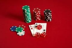 Chip ed assi di mazza su fondo rosso Gruppo di chip di mazza differenti Fondo del casinò Immagini Stock
