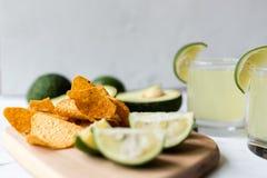 Chip freschi dell'avocado, della calce, della bevanda e del nacho che si trovano sul fondo di marmo Ricetta per il partito di Cin immagini stock libere da diritti