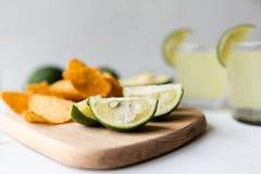 Chip freschi dell'avocado, della calce, della bevanda e del nacho che si trovano sul fondo di marmo Ricetta per il partito di Cin immagine stock