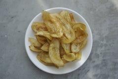 Chip fritti nel grasso bollente della banana sul piatto bianco fotografia stock libera da diritti