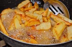 Chip fritti nel grasso bollente fatti casa. Immagini Stock