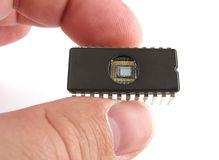 Chip in hand. An old eprom, with no branding held in the fingers stock photography