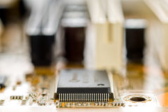 Chip set on circuit board. Chip set, focus on pins, on circuit board and blur electronic component in the background royalty free stock photo