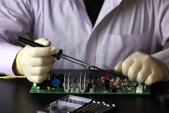 Chip soldering man hands Stock Image