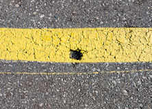 Chip in yellow painted asphalt Stock Image