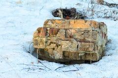 Chipbacksteinmauer, die aus dem Schnee heraus haftet Lizenzfreies Stockfoto