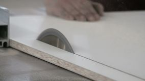 Chipboard sawing machine. A circular saw cuts off part of a white laminated wood sheet. Close-up. The real sound of a working wood. A circular saw cuts off part stock footage