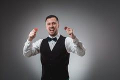 Chiper för en poker för man hållande övre röda poker Royaltyfri Fotografi
