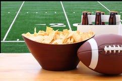 Chiper, fotboll och sex packe av öl och TV Arkivfoton