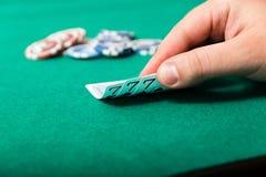 Chiper och kort för poker i hand på den gröna tabellen Arkivbilder