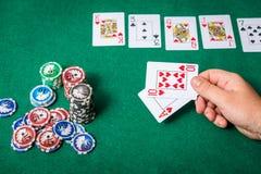 Chiper och kort för poker i hand på den gröna tabellen Royaltyfria Foton