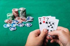 Chiper och kort för poker i hand på den gröna tabellen Royaltyfria Bilder