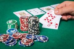 Chiper och kort för poker i hand på den gröna tabellen Royaltyfri Fotografi