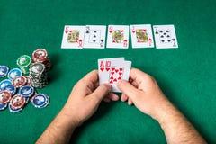 Chiper och kort för poker i hand på den gröna tabellen Fotografering för Bildbyråer