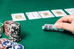 Chiper och kort för poker i hand på den gröna tabellen Arkivbild