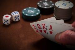 Chiper och kort för poker i hand på tabellen Royaltyfri Bild