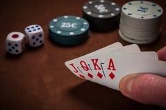 Chiper och kort för poker i hand på tabellen Arkivbilder
