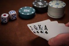 Chiper och kort för poker i hand på tabellen Arkivfoto