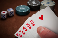Chiper och kort för poker i hand på tabellen Arkivfoton