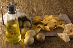 Chiper, rå potatis, ost och tillbringare av en olja royaltyfri bild