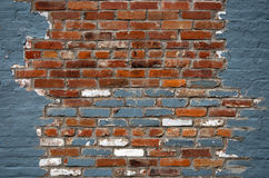 Chipped Away. Blue paint is chipped away from a brick wall Stock Image